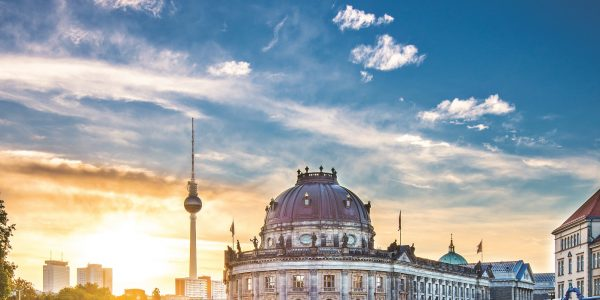 A view of Berlin, Germany including the Television Tower and Museum Island.  The sky overhead is blue and cloudy with hues of gold.